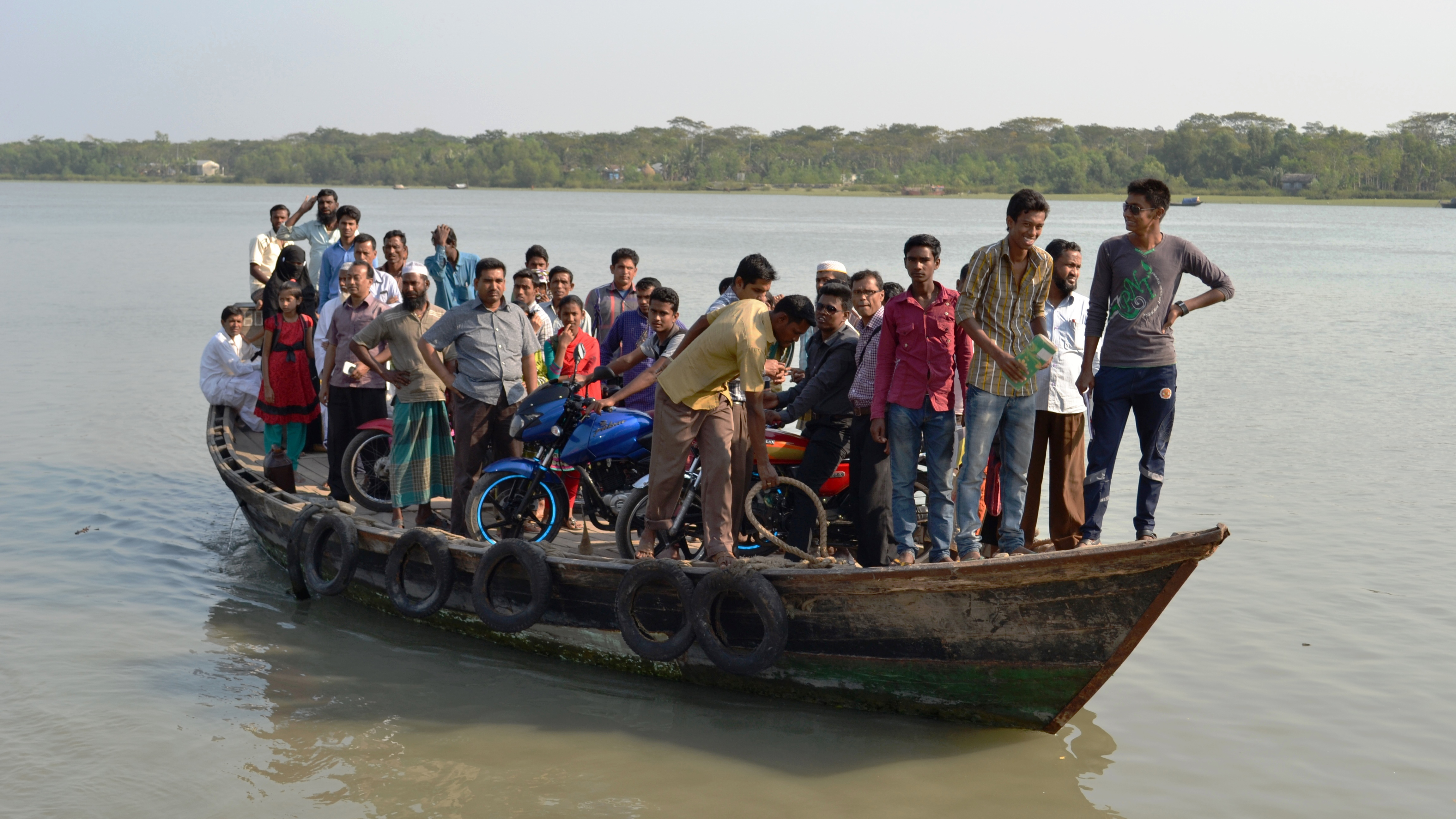 Lots of people on a small boat with their motorbikes waiting to disembark